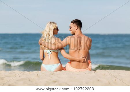 love, travel, tourism, summer and people concept - smiling couple on vacation in swimwear sitting and hugging on beach from back