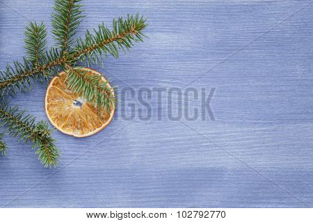 spruce twig with dried orange slices on blue table, christmas