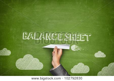 Balance sheet concept on blackboard with paper plane