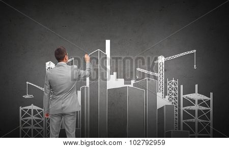 business, people, building, city and planning concept - businessman drawing construction site sketch from back over dark gray concrete wall background