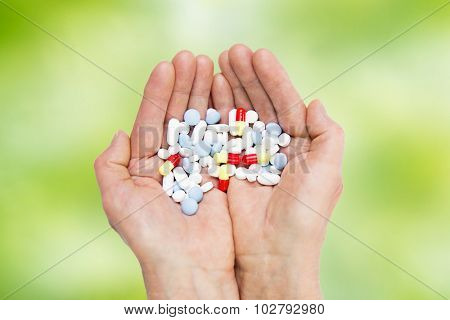 age, medicine, health care and people concept - close up of senior woman cupped hands with pills over green natural background