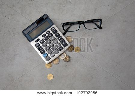 busines, finance, money and bookkeeping concept - calculator, eyeglasses and euro coins over gray concrete background