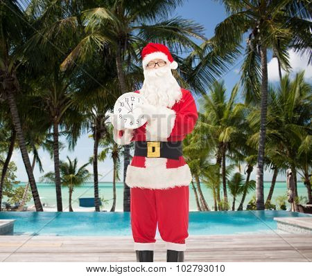 christmas, holidays, travel and people concept - man in costume of santa claus with clock showing twelve pointing finger over swimming pool on tropical beach background