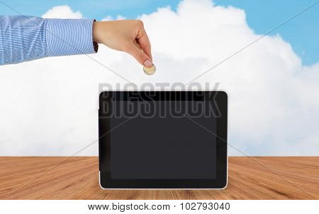 business, finance, investment, money saving and e-commerce concept - close up of hand putting coin into into tablet pc computer with black blank screen over blue sky and wooden floor background