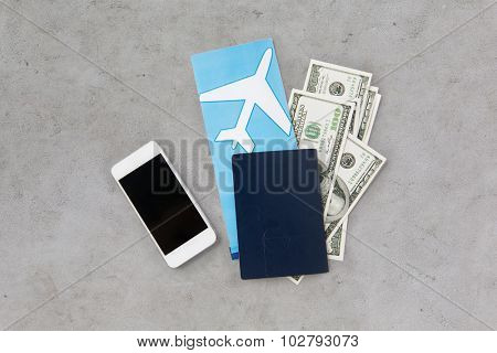 tourism, travel and objects concept - air ticket, money, smartphone and passport over gray concrete background