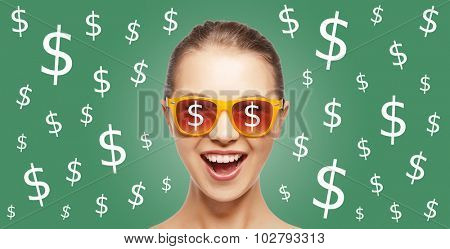 people, finance and money concept - happy screaming teenage girl in shades over green background with dollar currency sings