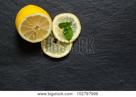 Half Of Lemon, Slices And Mint Leaves On A Slate Board
