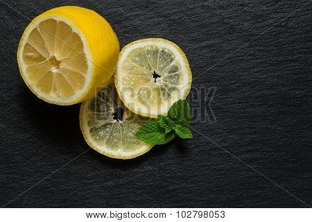 Slices And Half A Lemon With Mint Leaves On A Slate Blackboard