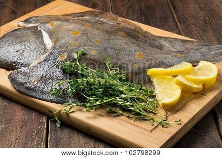 Raw Fresh Flounder With Thyme And Lemon On The Board