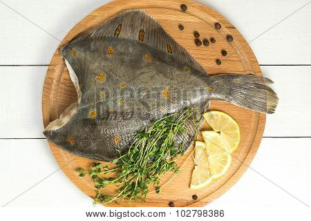 Crude Flatfish With Lemon, Thyme And Pepper On The Board