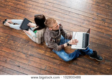 Girl using a tablet and boy using a laptop leaning on each other on wooden floor.