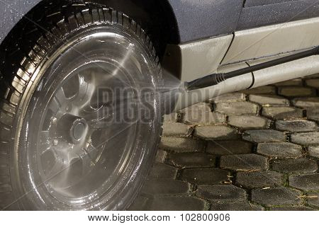 Black Car Tire Getting Detailed Wash From High Pressure Water Cleaner