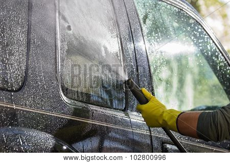 Arm With Yellow Glove Holding High Pressure Water Cleaner And Using It On Car Door Windows