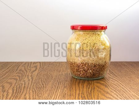 glass jar with mix of groats closed red cap on wooden table