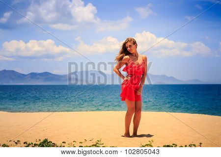 Blond Girl In Red Stands On Sand Holds Hand On Hip At Noon