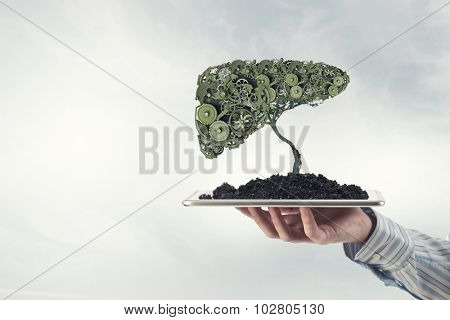 Environmental concept with hand hold green tree of industrial gear