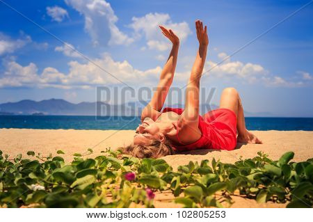 Girl In Red Lies On Sand Lifts Hands Near Foreground Creepers