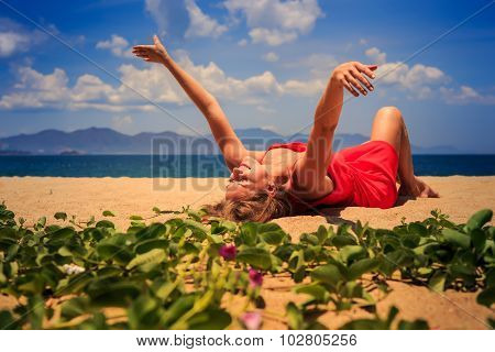 Girl In Red Lies On Sand Lifts Hands Aside Near Creepers