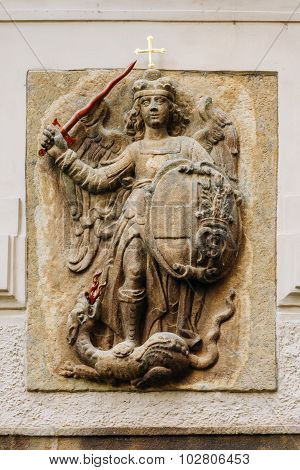Bas-relief of knight with a sword striking dragon in Prague, Cze