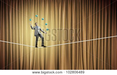 Young businessman balancing on rope and juggling with balls
