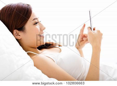 Smiling Young Woman Watching Smart Phone On The Bed