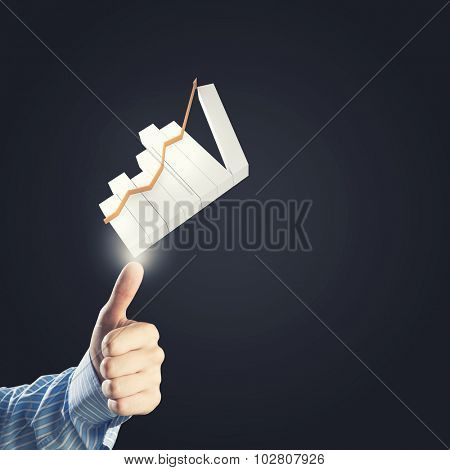 Close up of businessman's hand giving thumb up to rise on graph