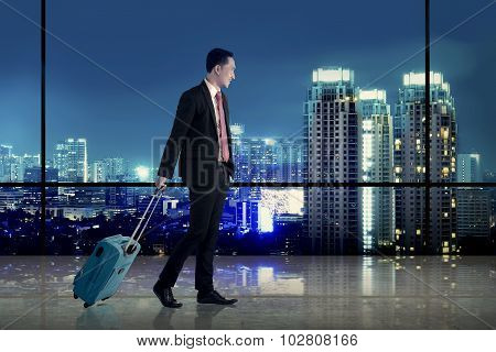 Business Man Walking With Suitcase Over City Background