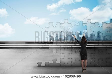 Asian Business Woman Holding Piece Of Puzzle Trying To Build A City