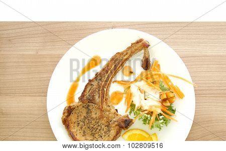 Grilled Pork Chop Steak. Colorful Salad And Orange Sauce