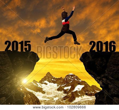 Girl jumps to the New Year 2016 at sunset. In the background Ober Gabelhorn - Pennine Alps, Switzerland.