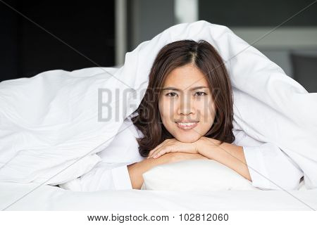 Asian Woman Lying At The End Of The Bed Underneath The Quilt And Smiling