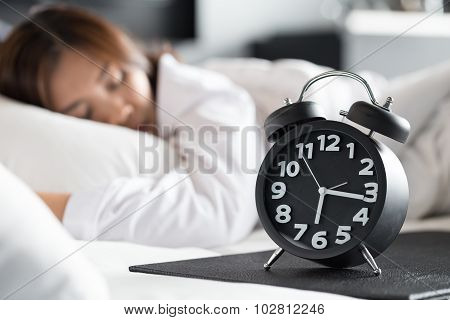 Asian Woman Sleeping On Bed And Wake Up With Alarm Clock