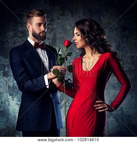 Young elegant couple in evening dress portrait. Woman in red sniff rose. Focus on woman.