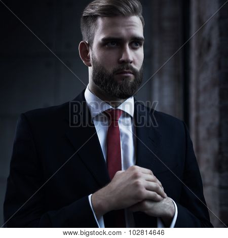 Young serious businessman with beard in black suit portrait.