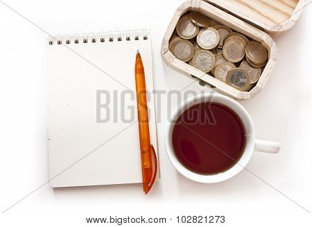 A spiral notebook with a place for text, a pen, a cup of tea and a small wooden box with money