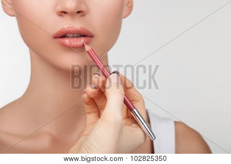 Cheerful young healthy woman is doing make-up