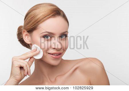 Beautiful young girl is washing make-up carefully