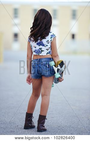 girl holding skate board