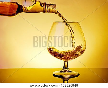 Barman Pouring Snifter Of Brandy In Elegant Typical Cognac Glass On Table