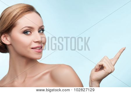 Attractive young woman is presenting something with joy