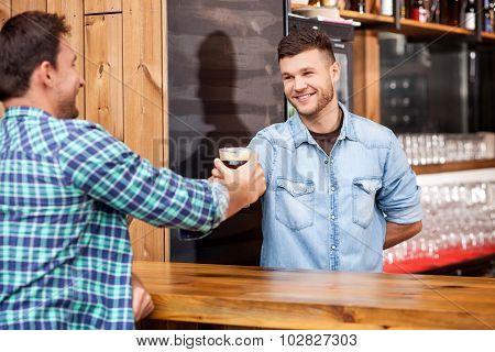 Handsome bartender is serving his customer in bar