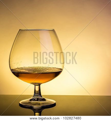 Snifter Of Brandy In Elegant Typical Cognac Glass On Table With Reflection