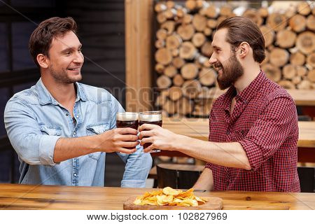 Cheerful friendly men are talking in pub