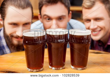 Attractive male friends are watching at drinks in bar
