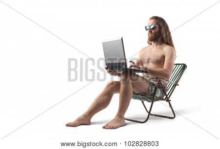 Man wearing a swim suit holding a laptop