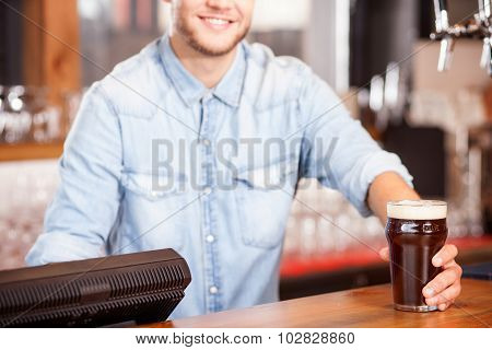 Cheerful young male bartender is serving customer in pub