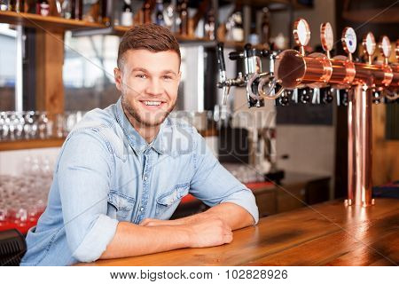 Cheerful young bartender is waiting for customer in pub