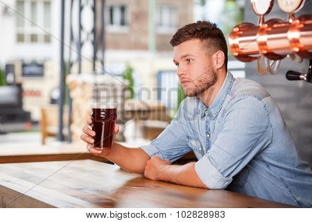 Attractive young barman is waiting for customers bar