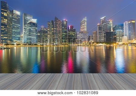 Opening wooden floor, Marina bay business office during twilight with water reflection