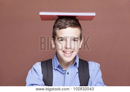 Male student holding textbooks over the head on brown background